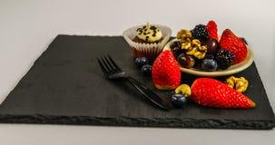 Insieme di vari dadi e frutta con il muffin del cioccolato con un bianco Immagini Stock Libere da Diritti