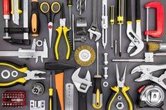 Insieme di vari strumenti del lavoro della mano sulla vista superiore del fondo grigio Fotografie Stock Libere da Diritti