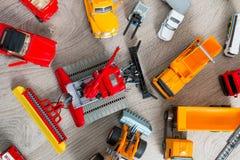Insieme di vario giocattolo giallo, rosso e bianco dell'automobile su fondo di legno grigio Vista superiore accumulazione Immagini Stock Libere da Diritti
