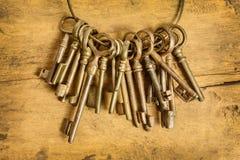 Insieme di vecchie chiavi su un fondo di legno Fotografie Stock
