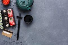 Insieme di vista superiore del maki e dei rotoli dei sushi con la teiera e carta di credito sul fondo rustico del sesamo e di gre Fotografia Stock