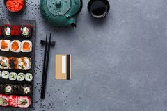 Insieme di vista superiore del maki e dei rotoli dei sushi con la teiera e carta di credito sul fondo rustico del sesamo e di gre Immagine Stock Libera da Diritti