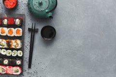 Insieme di vista superiore del maki e dei rotoli dei sushi sulla tavola grigia Immagine Stock