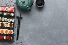 Insieme di vista superiore del maki e dei rotoli dei sushi sulla tavola grigia Fotografia Stock