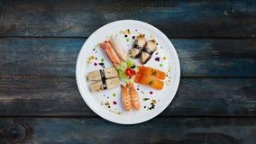 Insieme girante del sashimi su un piatto rotondo bianco, decorato con i piccoli fiori, alimento giapponese, vista superiore Prior stock footage