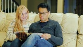 Insieme leggere una rivista La giovane coppia multi-etnica passa il tempo a casa stock footage