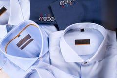 Insieme piano di disposizione dei vestiti degli uomini classici quali il vestito blu, le camice, le scarpe marroni, la cinghia ed Fotografia Stock