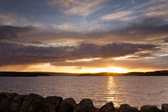 Insiemi di Sun sul bacino idrico di Kielder Fotografia Stock