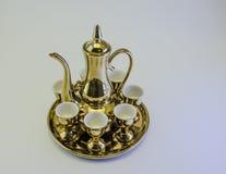 Insiemi di tè di vetro dell'oro del lanciatore isolati Fotografia Stock
