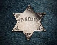 Insigne d'étoile de shérif sur le fond bleu de denim image libre de droits