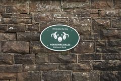 Insignes de parc national de vall?es de Yorkshire sur le mur en pierre - station de bosselure, Cumbria, R-U - 10 novembre 2017 photo stock