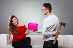 Insincire man holding axe giving gift box to woman Royalty Free Stock Photos
