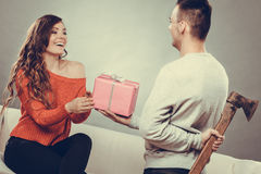 Insincire man holding axe giving gift box to woman Stock Images