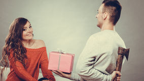 Insincire man holding axe giving gift box to woman. Sneaky insincere men holding axe giving gift present box to woman. Husband concealing hiding his true Royalty Free Stock Photos