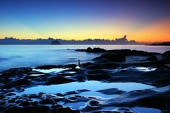 Insinuación de la salida del sol en costa en tono azul Fotos de archivo libres de regalías