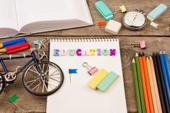 inskrift av & x22; education& x22; , cykelmodell, stoppur, bok, notepad och annan brevpapper på den bruna trätabellen arkivbilder