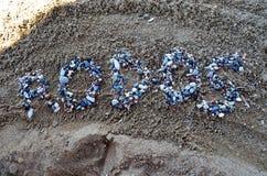 Inskrift av Rhodes med stenar på stranden royaltyfri foto