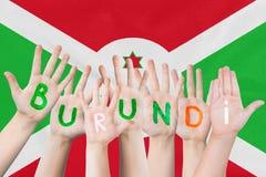 Inskrift Burundi på barnens händer mot bakgrunden av en vinkande flagga av Burundi royaltyfri foto
