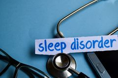 Inskrift för sömnoordning med sikten av stetoskopet, glasögon och smartphonen på den blåa bakgrunden royaltyfria bilder