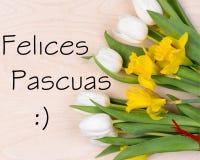 Inskrift Felices Pascuas med nya blommor Arkivbild