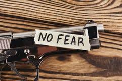 Inskrift INGEN SKRÄCK på sönderrivet papper och den glansiga pistolen arkivbild