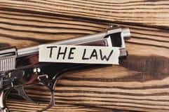 Inskrift LAGEN på sönderrivet papper och den glansiga pistolen royaltyfria bilder