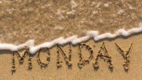 Inskrift MÅNDAG på en försiktig strandsand med den mjuka vågen Arkivbild