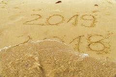 Inskrift 2018 och 2019 på en strandsand royaltyfri foto