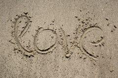 Inskrift på sand nära havet och vågor Förälskelse Arkivfoton