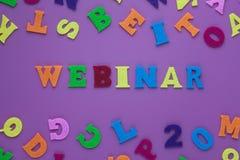 Inskrift som är webinar på en purpurfärgad bakgrund med mångfärgade bokstäver Ett begrepp för visning för ordhandstiltext av utbi arkivbild