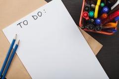 Inskrift som ska göras på det vita arket av papper och blyertspennor Arkivfoto
