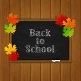 Inskrift tillbaka till skolan och lönnlöv på den svarta svart tavlan Arkivfoto