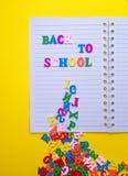 Inskrift tillbaka till skolan på en vit anteckningsbok Arkivbilder