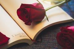 Inskriftanmärknings`en älskar jag dig mamma` inom den klassiska pappers- boken med den ljusa röda rosen Dag för Mather ` s, begre Arkivfoto