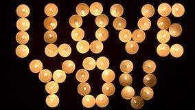 Inskriften ÄLSKAR JAG DIG som bildas, genom att bränna stearinljus på träbakgrunden