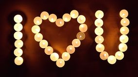 Inskriften ÄLSKAR JAG DIG som göras, genom att bränna stearinljus på träbakgrunden Begrepp för dag för valentin` s