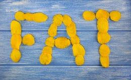 Inskriften av fett som läggas ut ur chiper på en blå träbakgrundsinskrift royaltyfria bilder