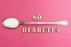 Inskriften 'den ingen sockersjukan, en sked med socker på en rosa bakgrund, begrepp royaltyfri foto