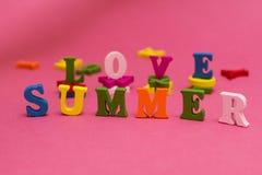 Inskriften 'förälskelse, sommar 'på en rosa bakgrund royaltyfria bilder