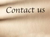 Inskriften kontaktar oss på ett ark av papper Arkivfoton