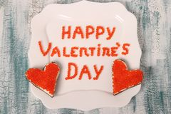 Inskriften 'lyckliga valentin dag 'från den röda kaviaren på en vit platta med canapes royaltyfria foton