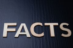"""Inskriften ordnas från bokstäver som klipps ut ur trä på tabellen Fakta för ordâ€en """" arkivbilder"""