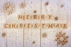 Inskriften på de kubbarnen lycklig jul På ett vitt träbakgrundshälsningkort övre sikt Arkivfoto
