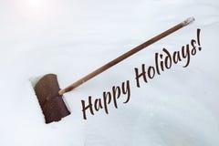 Inskriften på de lyckliga ferierna för snö Stor svart plast- skyffel i snödriva Rengöra av snö efter tungt snöfall skyffel royaltyfri fotografi