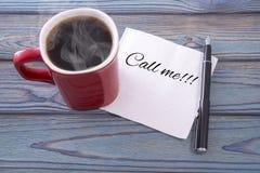 Inskriften på en servett kallar mig och kaffe i en röd kopp Royaltyfri Foto