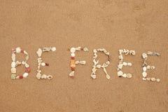 Inskriften som göras från skal på sand, är fri Fotografering för Bildbyråer