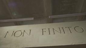 Inskriften som hjälpmedel är det inte slutet på den gråa väggen Isolerad NON FINITO-text, akronym av forntida Roman Empire Arkivfoto