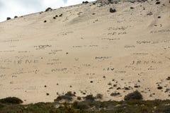 Inskrifter från stenar på stranden Playa de Sotavento, kanariefågelö Fuerteventura, Arkivfoton