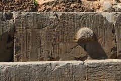 Inskrifter på en crepidoma på Delphi royaltyfria foton