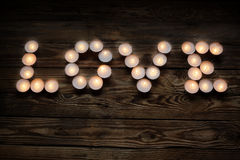 Inskriftförälskelse från stearinljus på träbakgrund Arkivbilder